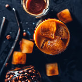 Iced coffee in a glass with ice cubes on black background,metal straw for cocktail, top view