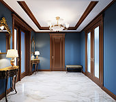 Fashionable, modern hall in a classic style house with blue walls, brown doors and white marble floor.