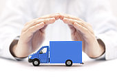 Blue cargo delivery truck protected by hands
