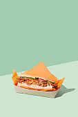 Vietnamese Banh Mi sandwich with roasted cauliflower and pickled veggie in takeaway packaging box on green background