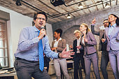Funny teambuilding activity. Business people singing karaoke in modern office