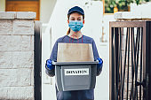 Volunteer young Caucasian girl in a protective medical mask and gloves with a donation box.