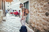 Handsome bearded tourist with backpack is making travel across city.