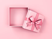 Blank pink pastel color present box or open gift box with pink ribbon and bow isolated on pink pastel color background with shadow top view