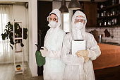 Specialists in protective suits take samples from surfaces in the home to test for a new corona virus.
