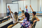 High school students raising hands on a class