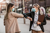 Businesswomen with safety masks greeting with elbow bump in front of office building.