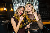 Portrait of happy young female friends together at nightclub