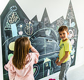 Brother and sister drawing on the blackboard Stock photo