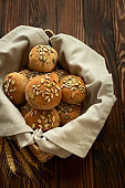 Basket of fresh homemade crispy bread buns with bran, sunflower and pumpkin seeds on brown wooden background. Top view.