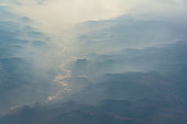 Sunrise above misty mountains from airplane window. Natural background.