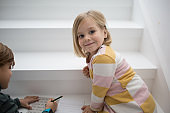 Playful adorable blonde girl sitting on stairs floor with older brother, drawing pictures together