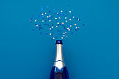 Champagne bottle with colorful confetti. Flat lay. Top view. Anniversary holiday celebration concept