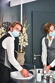 Young male wearing a surgical mask and a receptionist uniform looking at the camera while washing his hands. Hygiene and safety concept.