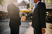 Corporate Businessmen Shaking Hands in Greeting Outdoors