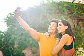 Embracing Male and Female Friends Taking Outdoor Selfie