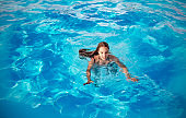 Teenage girl swims in the clear blue water
