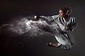 Karate girl bounces and makes a kick