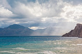 Sandy beach with mountains and cloudy sky