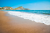 Sandy beach with mountains and blue sky