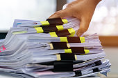 Businessman hands working in stacks documents of paper files, searching information on desk office, Accounting budget report file, check working for arranging unfinished of paperwork on busy office