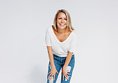 Blonde hair happy woman 35 year plus in white t-shirt and blue jeans isolated on white background