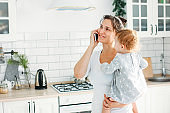 Young woman mom with baby girl on hands using mobile on bright kitchen at home