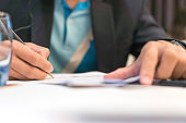 Businessman manager signing Document report and business note in meeting room concept: Start up writing for reading and learning in paperwork or documentation files at corporate office background.