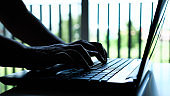 Silhouette hands of hacker or cyber crime typing coding keys on laptop keyboard, Attack signifying internet theft while using online banking, anonymous business in technology networking concept