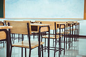 Lecture room, School empty classroom with desk chair iron wood for studying lessons in high school. No student in situation of Covid-19 disease outbreak result in inability organize teaching learning