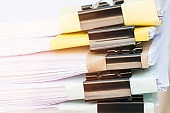 Unfinished documents stacks of paper files on office desk for report papers, piles of unfinish sheet achieves with black clips. Document is written presented. Business offices busy concept.