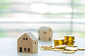 Home real estate mortgage concept : House miniature model with stack money coins show for selling. Ideas for offers of mortgage loan investment, management agreement building to buy new residential