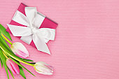 Gift box and tulip flowers on pink paper