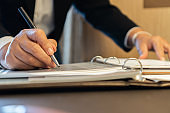 Signing Document report and business busy concept: Businessman manager hands holding blue pen for reading and sign in paperwork or documentation files on computer modern corporate office background.