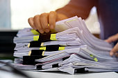 Stacks documents of paper files, Businessman hands working in messy bureaucracy and searching information on office, Accounting budget report file, arranging unfinished of paperwork on busy overwork