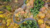 Aerial view of curvy road in forest. Autumn high in mountains. Cars passing each other