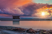 wooden shed by the sea at dawn with dramatic sky