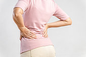 Young woman feeling pain in her back on white background. Healthcare and medical concept.