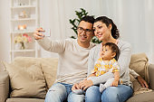 mother and father with baby taking selfie at home