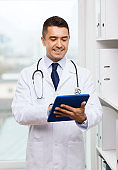 smiling male doctor in white coat with tablet pc