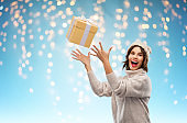 young woman in winter hat catching gift box