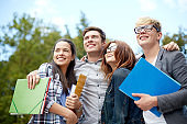 group of happy students with folders outdoors