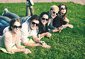 group of happy smiling teenage friends lying on grass