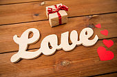 close up of word love with gift box and red hearts