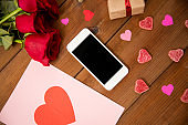 close up of smartphone, gift, red roses and hearts