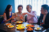 Asian senior woman taking food photo before a meal with her family.