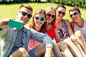 smiling friends with smartphone sitting on grass