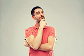 man in polo t-shirt thinking over gray background