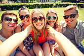 group of smiling friends making selfie in park