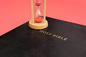 Holy Bible, the Word of God with hourglass. Isolated on pink background. Top view. Close-up. Horizontal shot